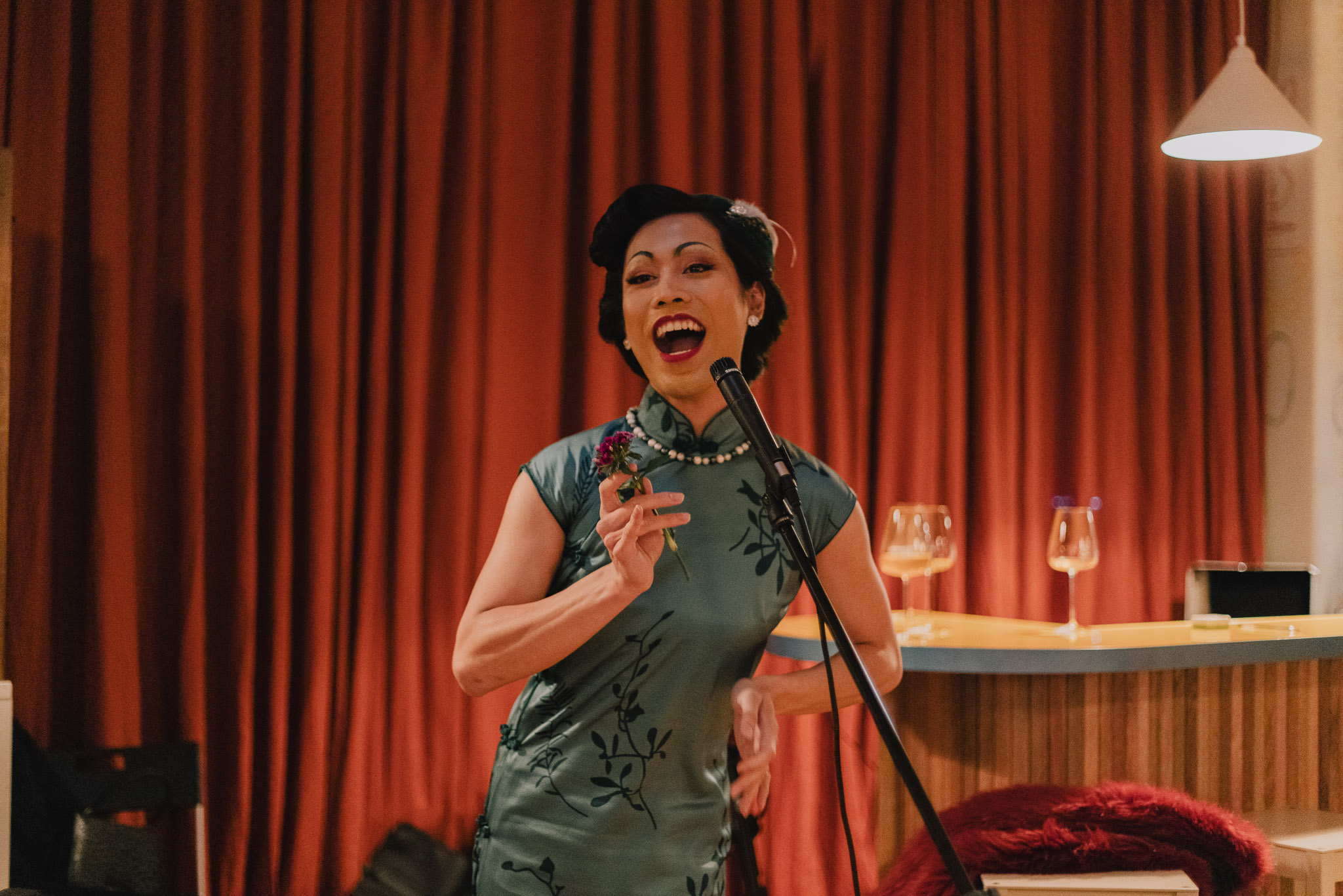 image of a performer wearing a cheongsam and lip syncing into the microphone