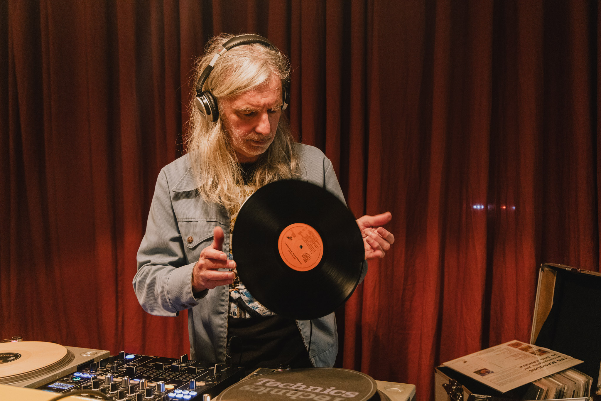 image of a person with long white hair holding a vinyl record while djing