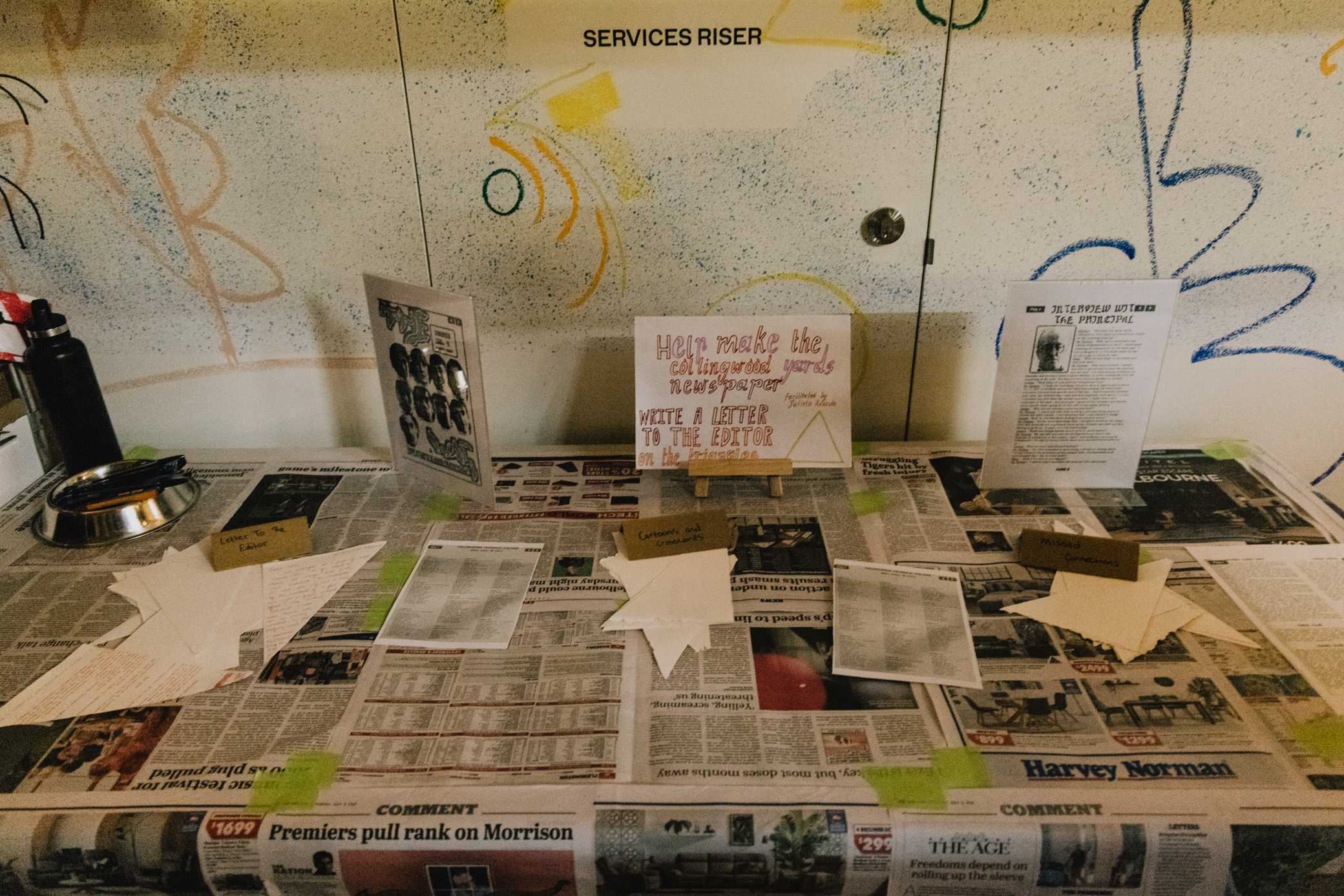 a table covered in newspaper with notes and signs